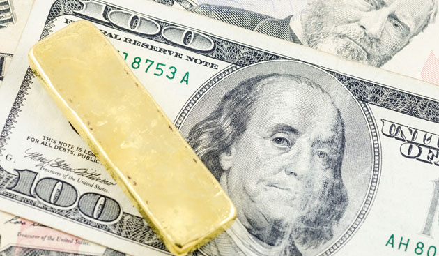 Gold bar and dollars